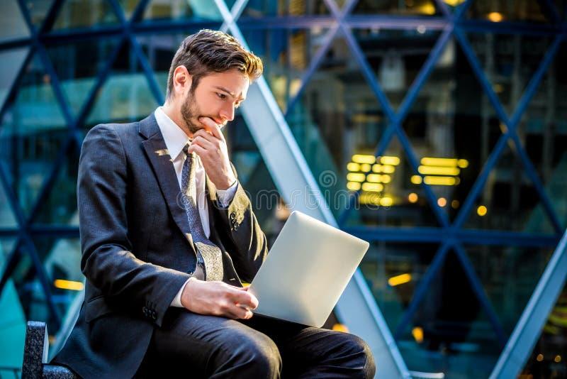 Worried businessman on laptop computer stock photo