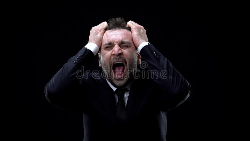 Worried businessman shouting on dark background, mental exhaustion, pressure. Stock photo stock photography