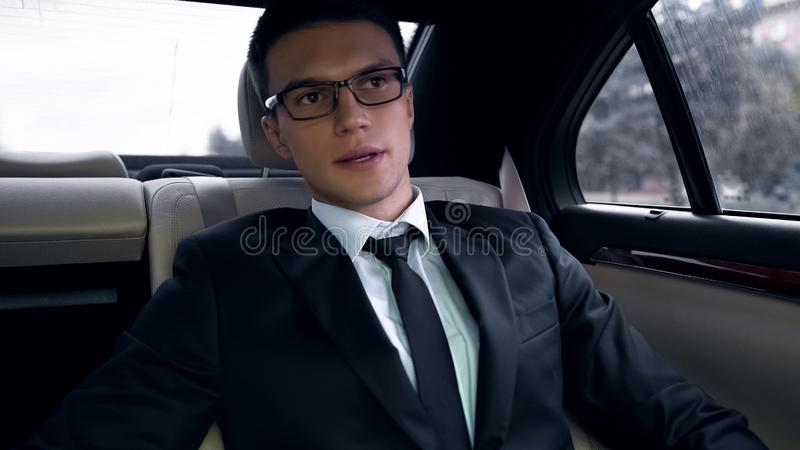 Worried businessman sitting on backseat of luxury car, late for work, rush hour royalty free stock photography