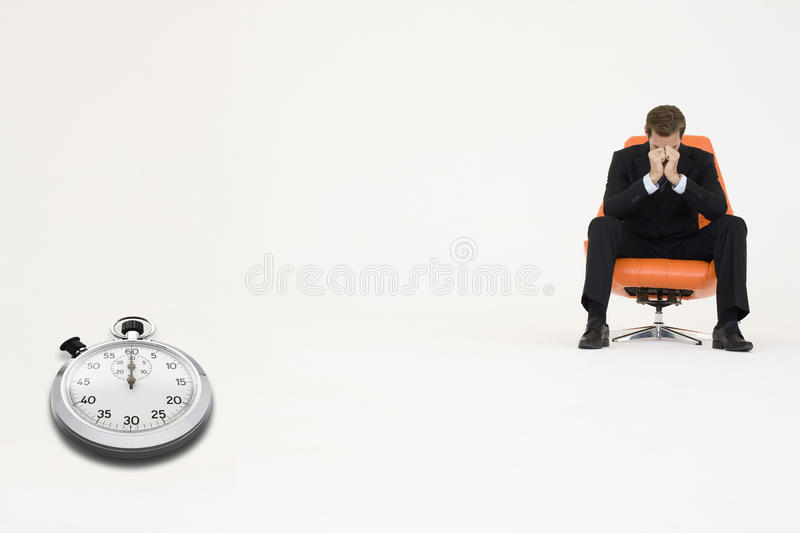 Worried businessman sitting on chair with stopwatch representing loss of time stock image
