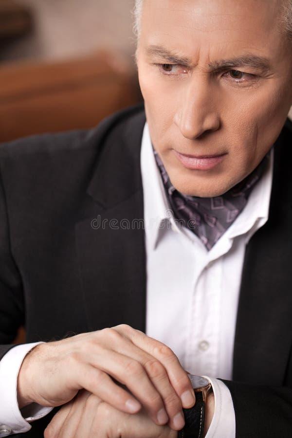 Worried businessman. Worried mature businessman checking the tim stock photo