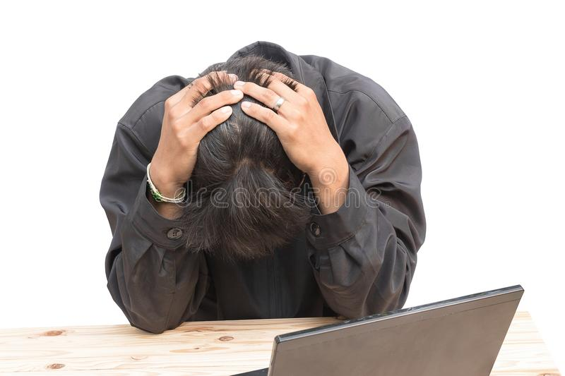 Worried businessman . a young man sits at his Desk and holds his hands on his head stock photo