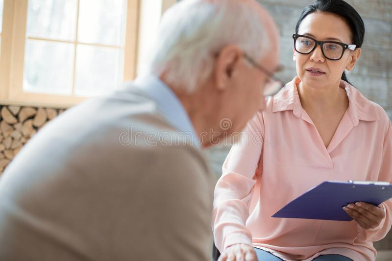 Worried caregiver giving care to senior man. Responsibility of caregiver. Appealing asian caregiver holding clipboard while wearing glasses and calming down stock photo