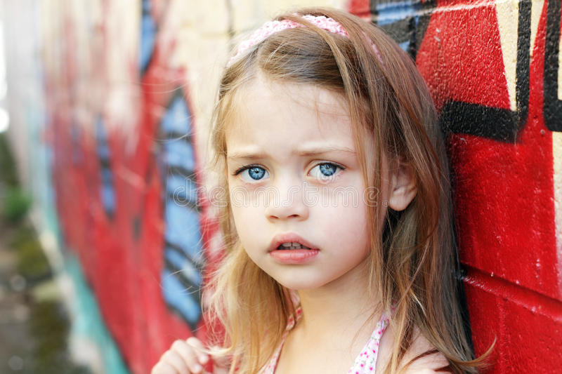 Worried Child. Worried little girl in an urban setting looking into the camera stock photos