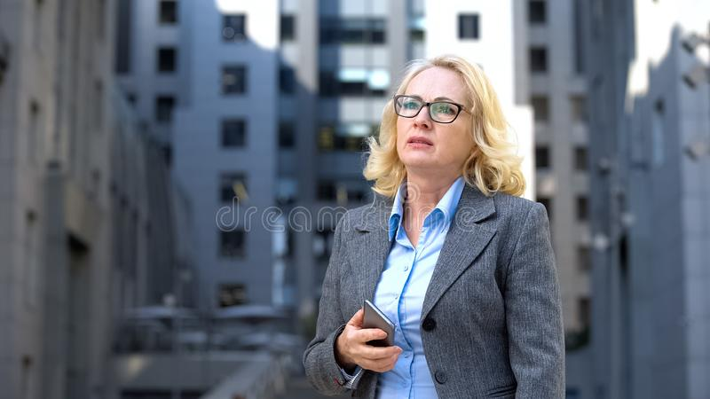 Worried company manager holding smartphone thinking of work problem outdoors royalty free stock photography