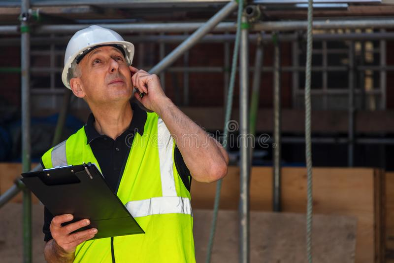 Worried Male Builder Architect Contractor on Building Site Using Phone royalty free stock images