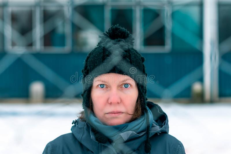 Worried concerned serious woman behind chain-link fence royalty free stock photo
