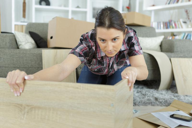 Worried confused woman assembling furniture. Female stock images