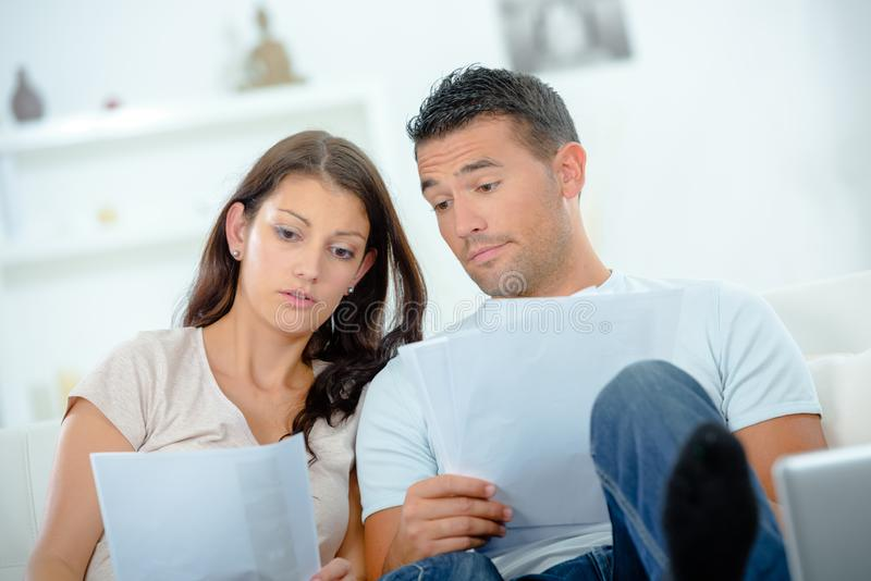 Worried couple after calculating bills sitting at home stock photo