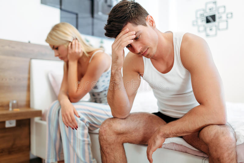 Worried couple having problems in bedroom stock photos