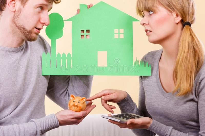 Worried couple with house. Home real estate credit mortgage concept. Worried couple with house. Young men and women holding building cutout and calculator stock photo