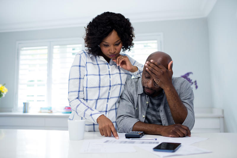 Worried couple interacting while checking the bills stock photography