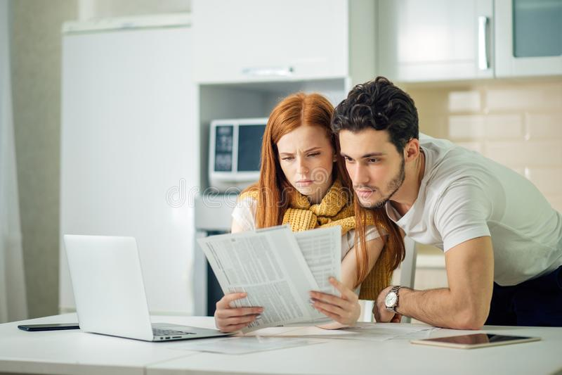 Worried couple paying their bills online with laptop at home in living room stock photos