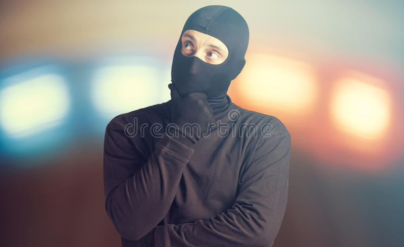 Worried criminal. Worried masked criminal thinking for alternatives royalty free stock photography