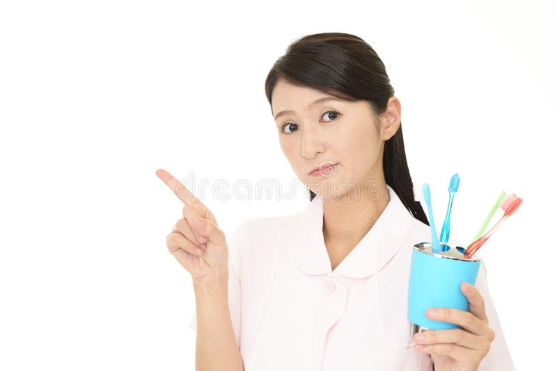 Worried dental hygienist. Dental hygienist pointing isolated on white background royalty free stock image
