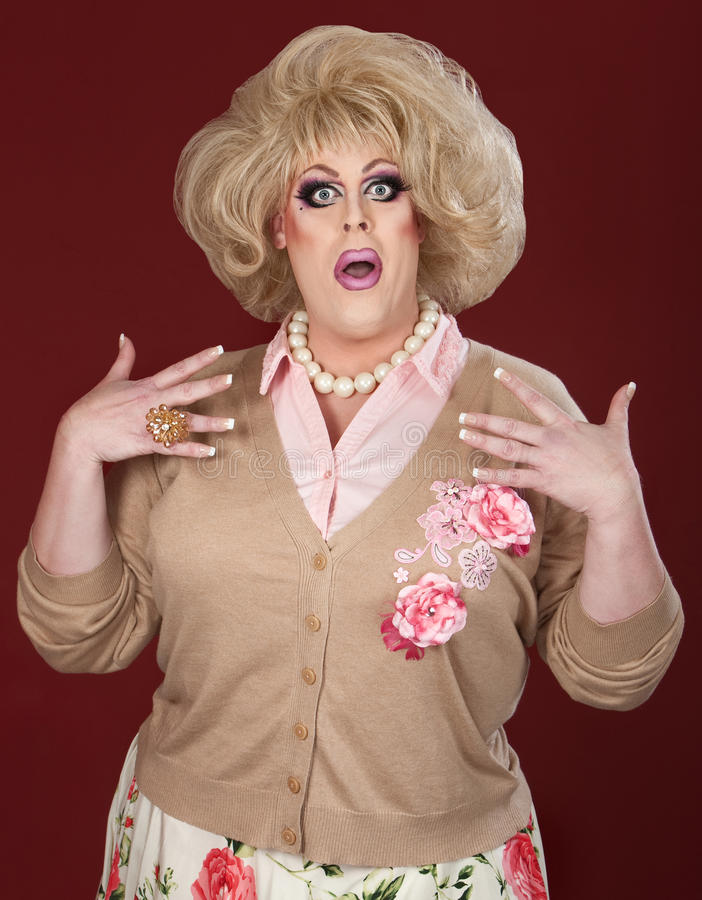 Worried Drag Queen. Worried male drag queen over maroon background stock photo