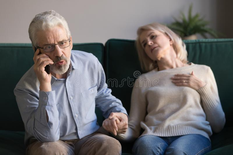 Worried elderly husband call emergency for sick wife royalty free stock images