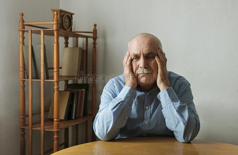 Worried elderly man with his head in his hands stock photo