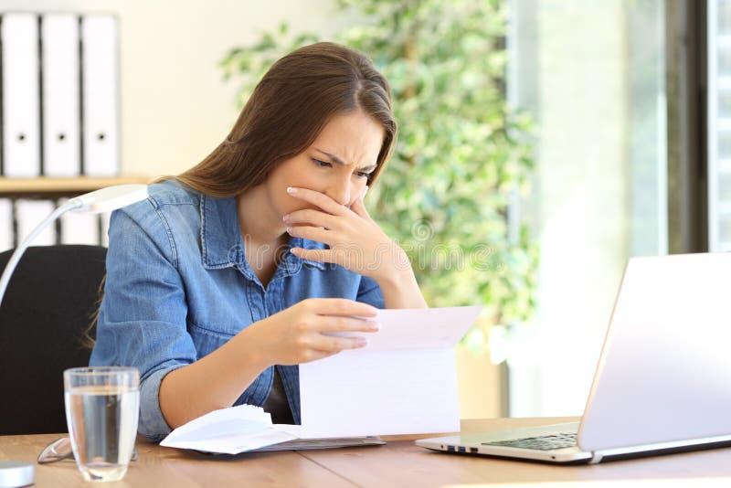 Worried entrepreneur girl reading a letter stock image