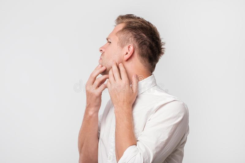 Worried european guy in white shirt touching his cheek and look confused. Have problem with dry skin royalty free stock image
