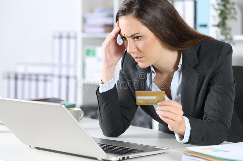 Worried executive paying with card on laptop at office royalty free stock photos