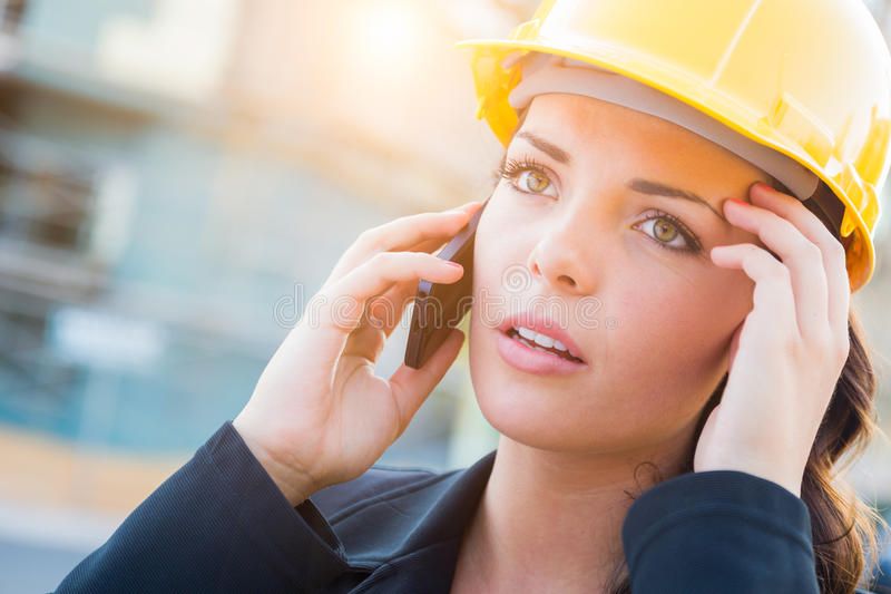Worried Female Contractor Wearing Hard Hat on Site Using Cell Ph stock image