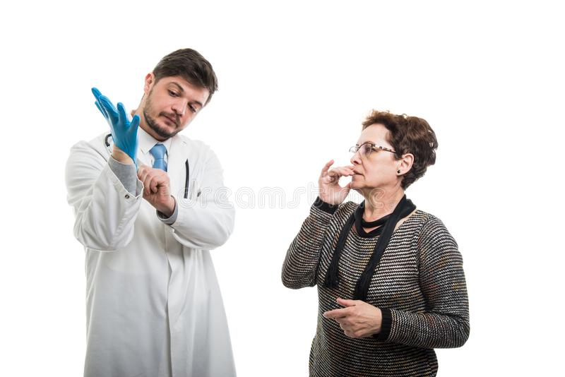 Worried female patient looking to male doctor putting blue glove stock image