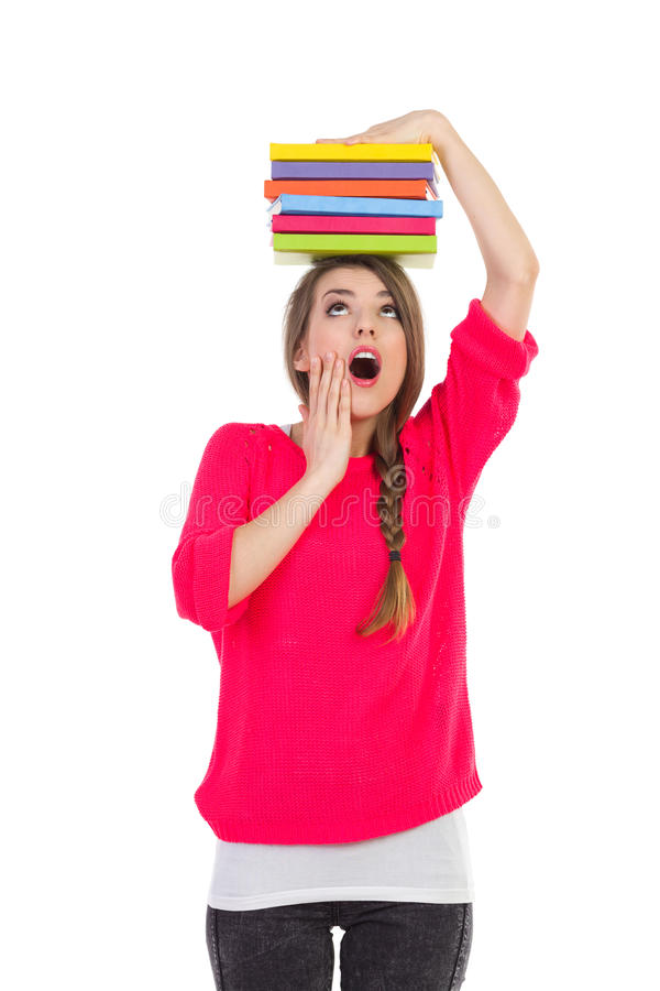 Worried female student. Worried young woman holding stack of book on her head. Three quarter length studio shot isolated on white royalty free stock image