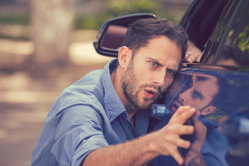 Worried funny looking man obsessing about cleanliness of his new car. Young worried funny looking man obsessing about cleanliness of his new car on a summer day royalty free stock photography