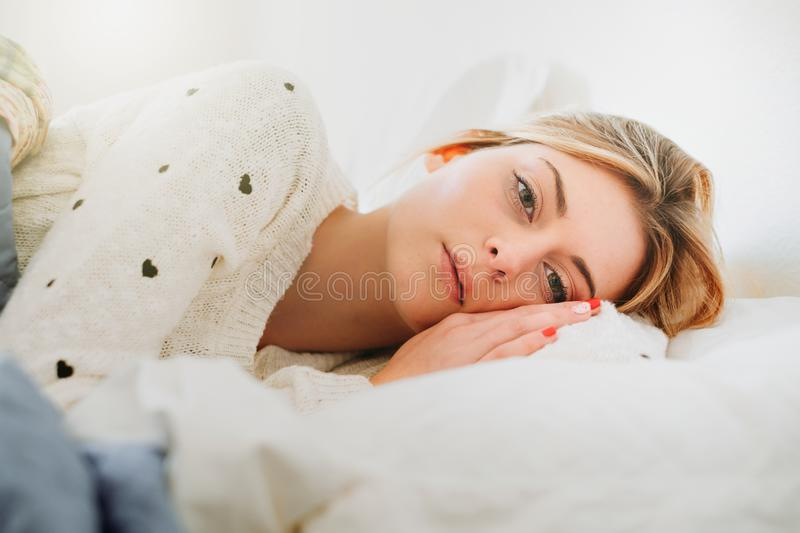 Worried girl lying on the bed in the morning light royalty free stock image