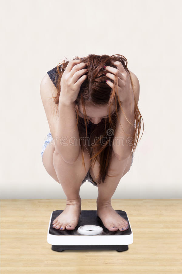 Worried girl measure her weight royalty free stock image