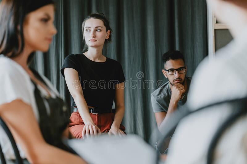 Worried girl on psychotherapy. Young worried girl sitting on a group psychotherapy with friends royalty free stock images