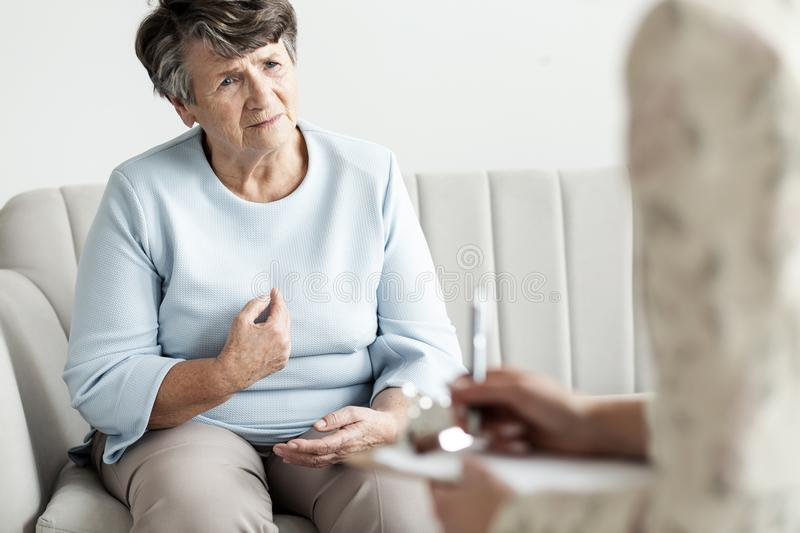 Worried grandmother talking to a financial advisor about her deb stock image