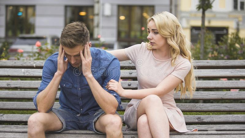 Worried guy sitting on bench, girlfriend calming him down, problems and support stock images