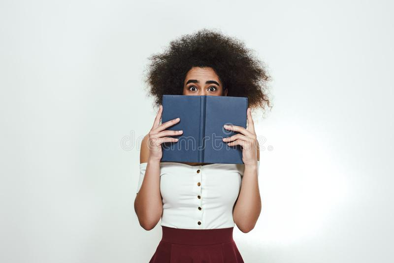 Worried about her exams. Frustrated young african woman holding book and covering her face with it while standing stock photos