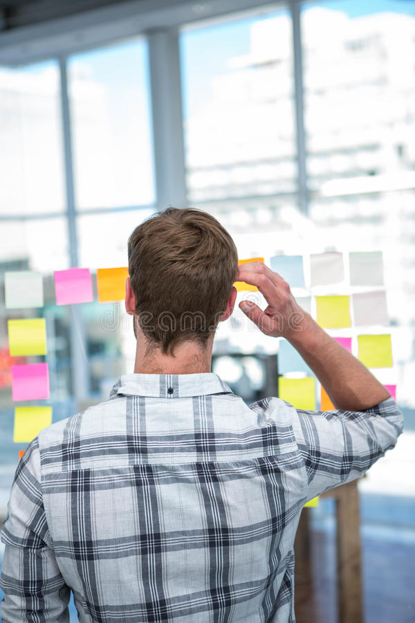 Worried hipster man in front of post-it stock image