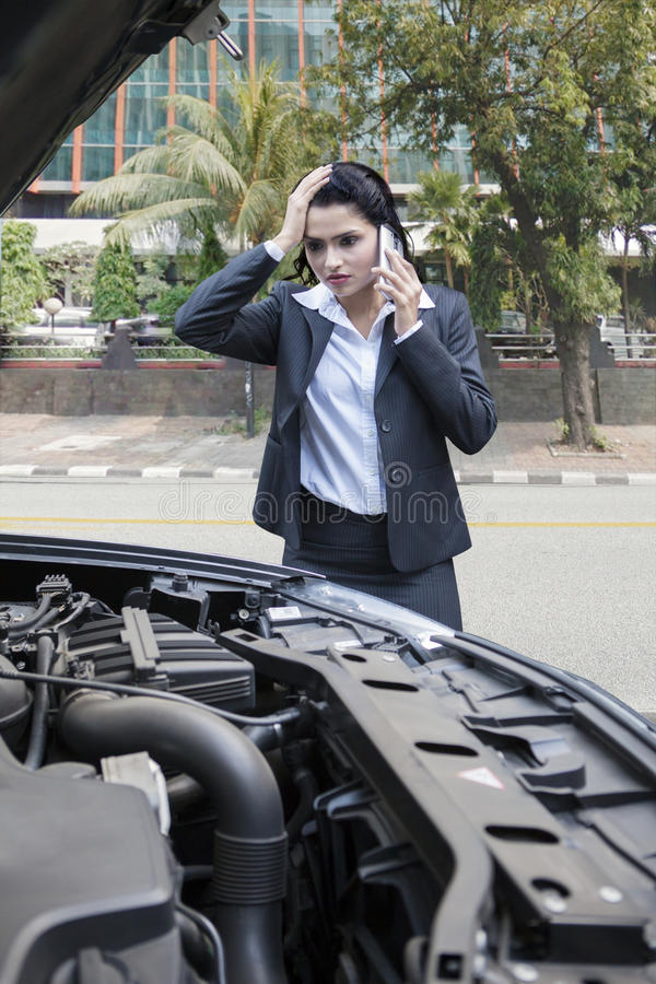 Worried indian businesswoman with broken car stock images