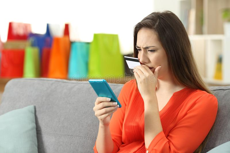 Worried lady buying online with credit card and phone stock image