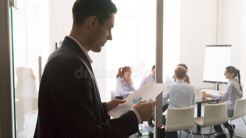Worried male presenter reading paperwork before presentation. Worried male worker stand outside conference room reading paperwork project report get ready for stock photo