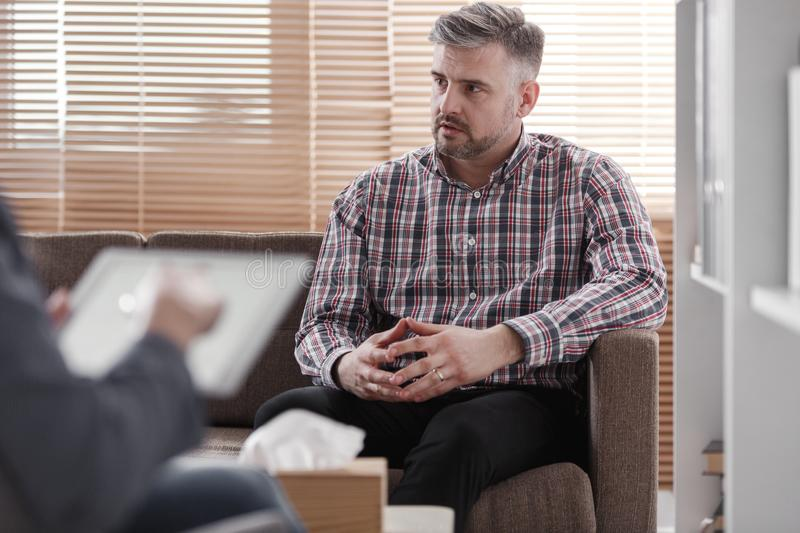 Worried man consulting marital problem. Worried men consulting on a marital problem during therapy with a counselor royalty free stock photography