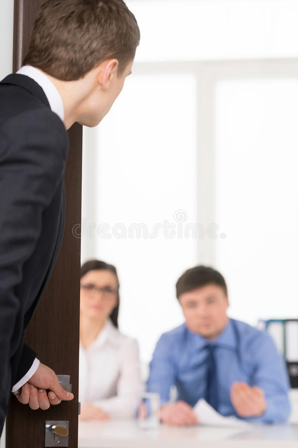 Worried man entering a room for job interview. Two Human Recourses Agent sitting in office. Blur background royalty free stock images