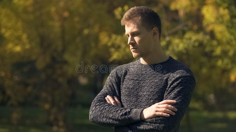 Worried man feeling insecurities in autumn park, life difficulties, problem. Stock photo royalty free stock image