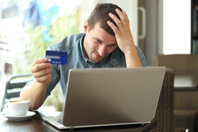 Worried man having problems paying with credit card and laptop. Sitting in a coffee shop royalty free stock photography