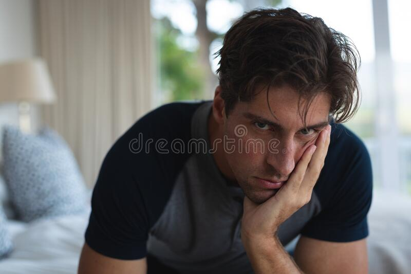 Worried man head in hands on the bed at home. Front view close up of a distressed Caucasian man at home, sitting on his bed, leaning his head on his hand and royalty free stock image