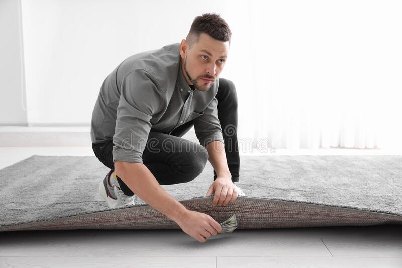 Worried man hiding money under carpet. Financial savings royalty free stock images