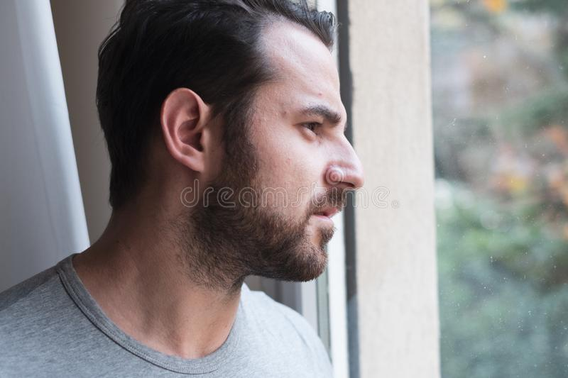 Worried man looking thoughtful out of window royalty free stock photos