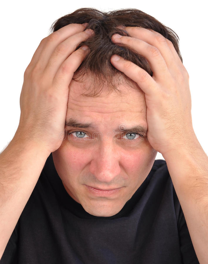 Worried Man with Stress Closeup. A middle aged man has stress and worry and he is holding his hands on his head, in his hair. Use it for a headache, money royalty free stock image