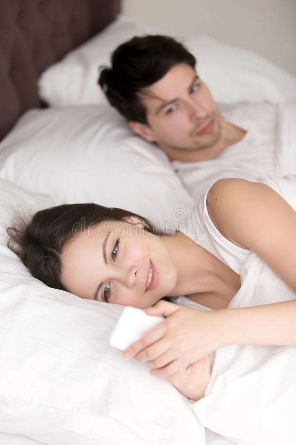 Worried man suspecting his girlfriend cheating using cellphone i royalty free stock photography