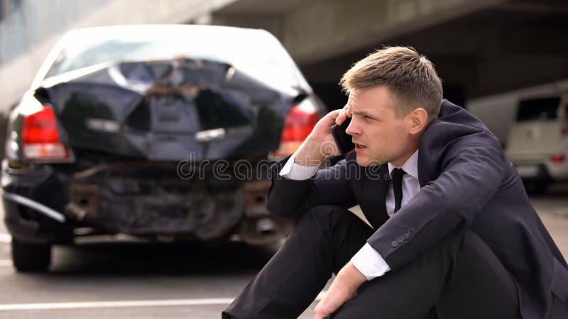 Worried man talking on phone outdoors broken auto background, traffic collision. Stock photo stock photos