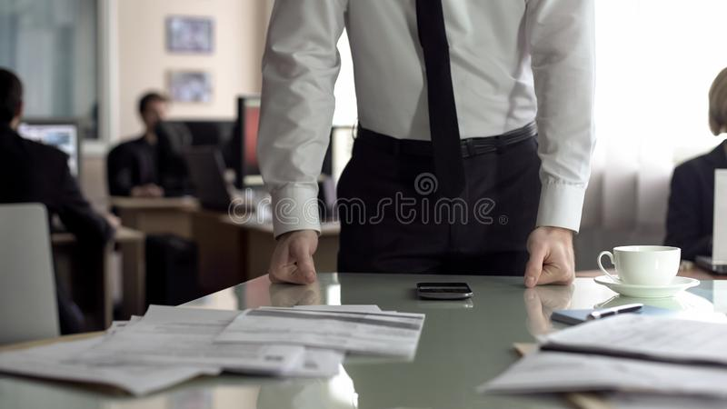 Worried manager leaning on table, frustrated after phone talk, problems at work. Stock photo royalty free stock photo